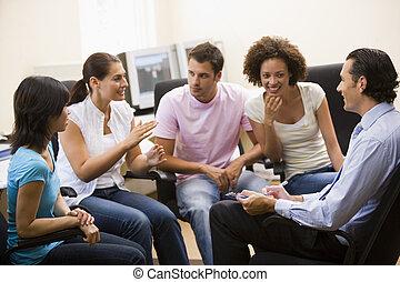 Un hombre dando conferencias a cuatro personas en la sala de computadoras