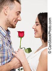 Un hombre dando una rosa a su amada