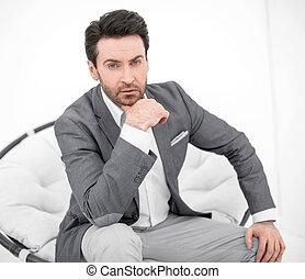 Un hombre de negocios atento sentado en una silla