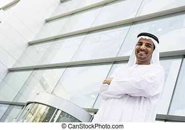 Un hombre de negocios de Oriente Medio parado frente a una oficina