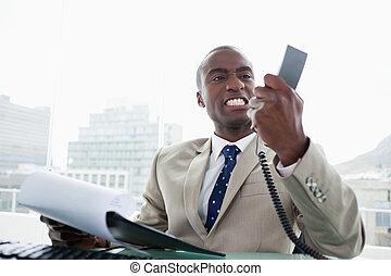 Un hombre de negocios enojado mirando su teléfono