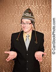 Un hombre de negocios gracioso en el encogimiento de la gorra de punto