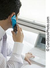 Un hombre de negocios haciendo una llamada mientras miraba a PC