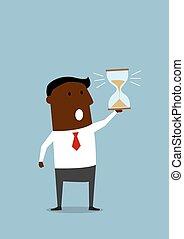 Un hombre de negocios negro con reloj de arena en la mano