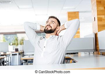 Un hombre de negocios relajado sentado en el cargo con las manos detrás de la cabeza