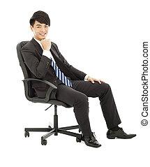Un hombre de negocios seguro sentado en una silla
