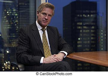 Un hombre de negocios sentado en la mesa mirando la cámara