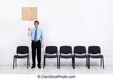 Un hombre de negocios solitario o un empleado sosteniendo pancarta