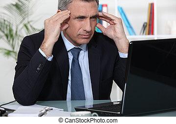 Un hombre de negocios tenso se sentó en el escritorio