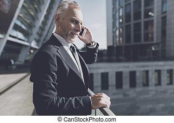 Un hombre de traje negro hablando por teléfono.