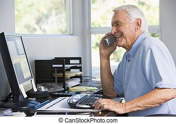Un hombre en la oficina central por teléfono usando una computadora sonriendo