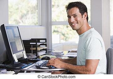 Un hombre en la oficina usando computadora y sonriendo