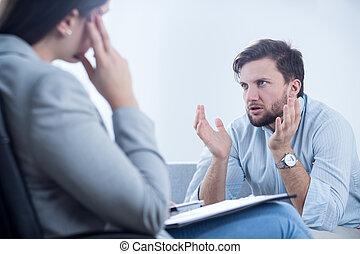 Un hombre enfadado hablando con un psiquiatra