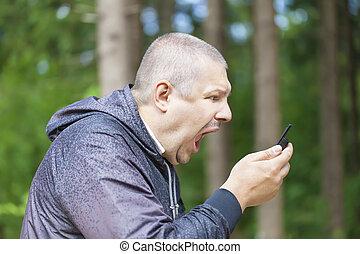 Un hombre enojado gritando por teléfono