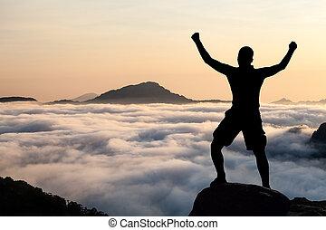 Un hombre escalando silueta en las montañas