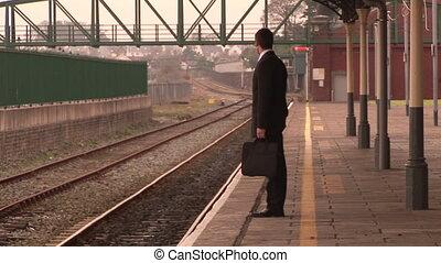 Un hombre esperando en una estación de tren