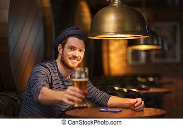 Un hombre feliz bebiendo cerveza en un bar o un pub