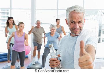 Un hombre feliz con pulgares arriba con gente ejerciendo en el fondo en el estudio de fitness