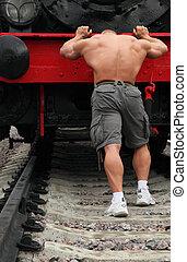 Un hombre fuerte sin camisa empuja la locomotora