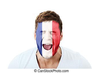Un hombre gritando con bandera francesa en la cara.