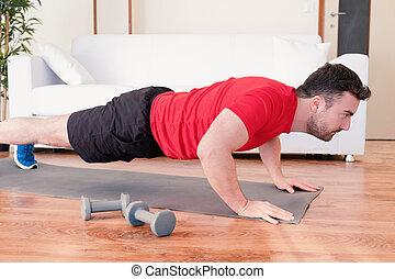 Un hombre guapo ejercitando con flexiones en casa