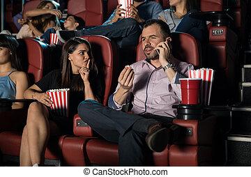 Un hombre hablando por teléfono en el cine
