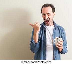 Un hombre mayor bebiendo café en una taza apuntando con la mano y el dedo con cara feliz sonriendo