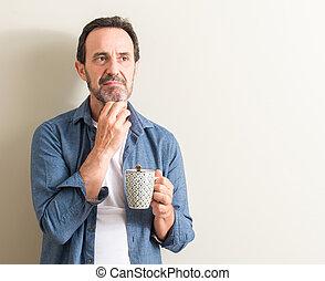 Un hombre mayor bebiendo café en una taza con cara seria pensando en la pregunta, una idea muy confusa