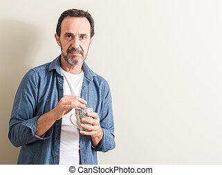 Un hombre mayor bebiendo café en una taza con una expresión segura en cara inteligente pensando en serio