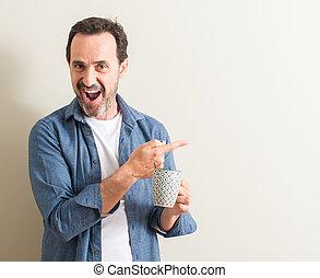 Un hombre mayor bebiendo café en una taza muy feliz señalando con la mano y el dedo a un lado