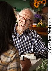 Un hombre mayor en casa con cuidador o cuidador