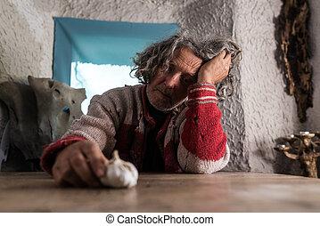 Un hombre mayor mirando una bombilla de ajo fresco