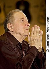 Un hombre mayor rezando en la iglesia