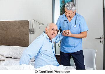 Un hombre mayor siendo asistido por un cuidador masculino en el dormitorio