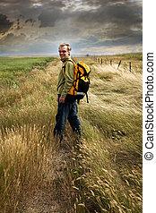 Un hombre mirando atrás y sonriendo en un camino de campo