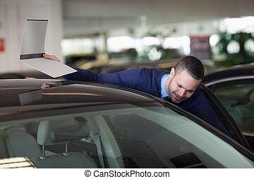 Un hombre mirando dentro del auto