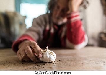 Un hombre mirando una bombilla cultivada de ajo fresco