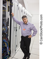 Un hombre parado junto a una torre de servidores