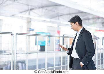 Un hombre que usa tablet en la estación de tren