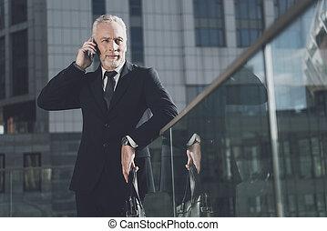 Un hombre respetable con barba en traje de negocios hablando por teléfono