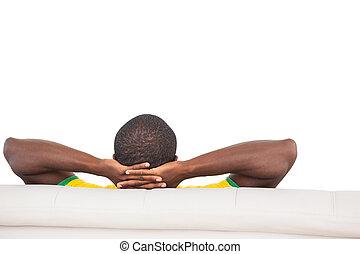 Un hombre sentado en el sofá con las manos detrás de la cabeza