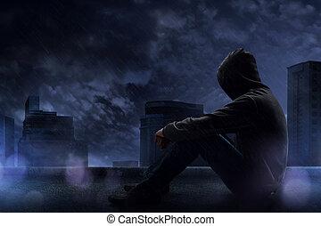 Un hombre sentado en la azotea en una noche lluviosa