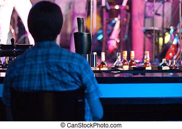Un hombre sentado en un bar
