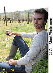 Un hombre sentado en un viñedo