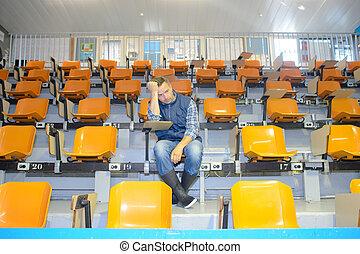 Un hombre sentado solo en el auditorio