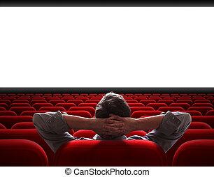 Un hombre sentado solo en una sala de cine vacía