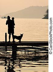 Un hombre sosteniendo a un niño en el muelle de madera durante el atardecer con mascota, escena familiar