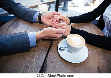 Un hombre sosteniendo la mano de su novia en el restaurante