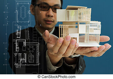 Un hombre sosteniendo un modelo de casa en sus manos.
