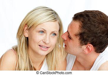 Un hombre susurrando a una mujer algo gracioso